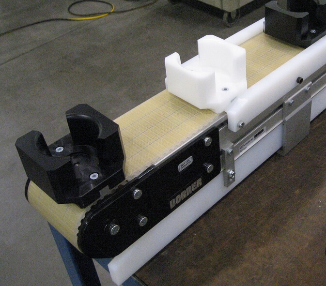 Precision move belt conveyor with fix mounted holders on the belt for accurate control of products.
