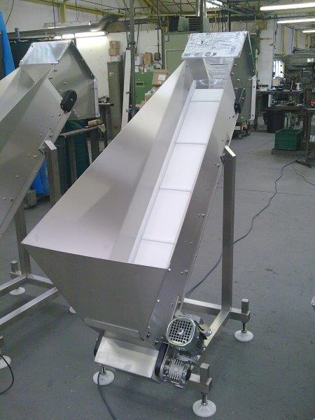 Elevating stainless steel belt conveyor with hopper.
