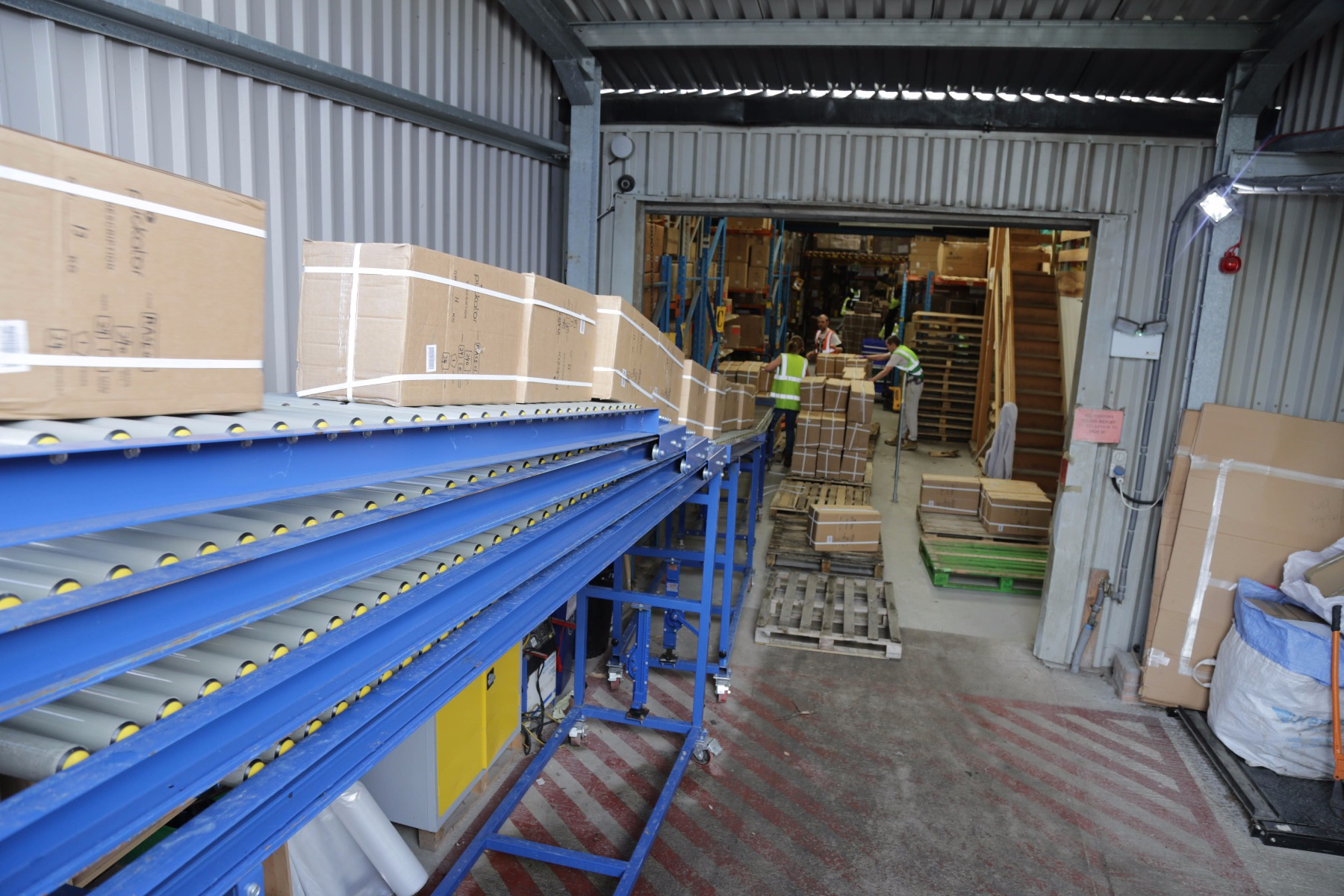 Extendable roller conveyor for unloading vehicles